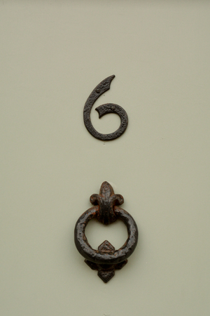 House number 6 sign on door with door knocker