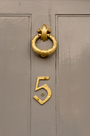 House number 5 sign on door with brass door knocker