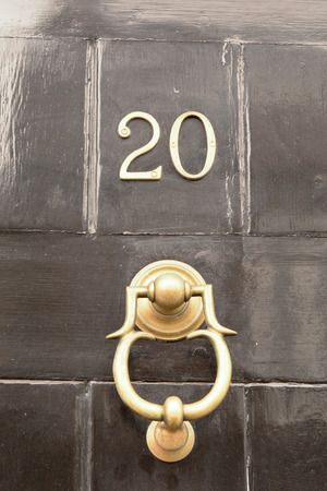 House number 20 sign on black door with brass door knocker