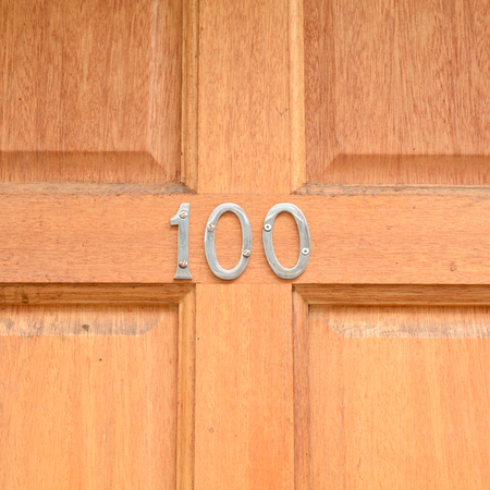 House number 100 sign on wooden door Stock Photo
