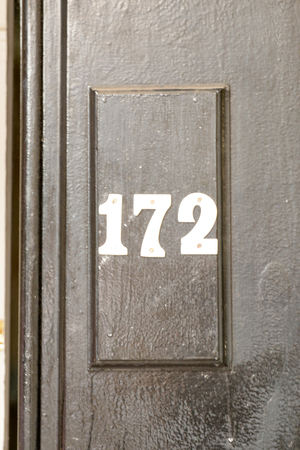 House number 172 sign on black painted door Stock Photo