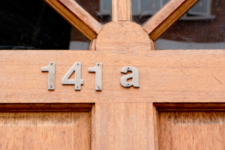 House number 141A sign on wooden door