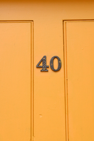 House number 40 sign on yellow painted door