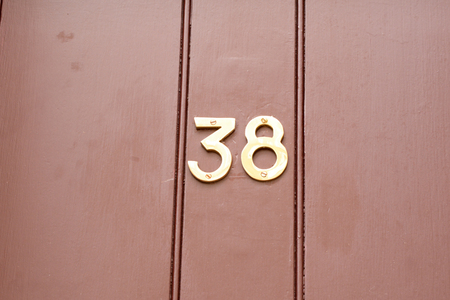 House number 38 sign on red painted door Stock Photo