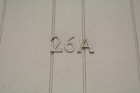 House number 26A sign on green painted door