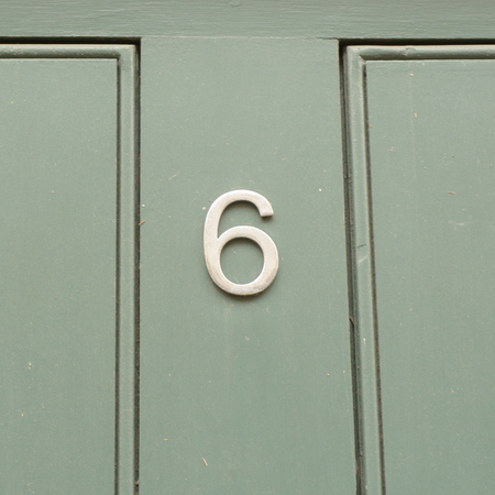 House number 6 sign on green painted door Stock Photo