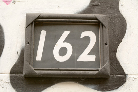 House number 162 sign on wall