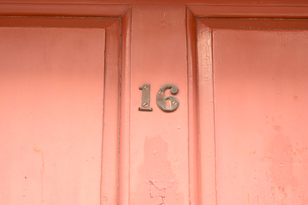 House number 16 sign on red painted door