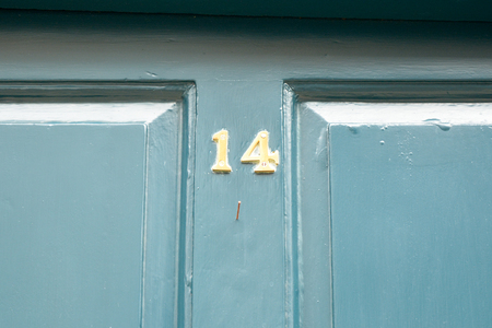 House number 14 sign on blue painted door