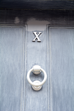 House number 10 sign shown as Roman numeral X on blue painted door