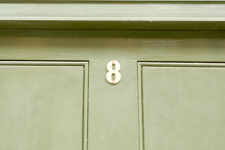 House number 8 sign on green painted door