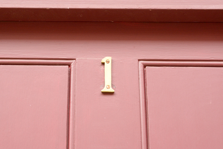 House number 1 sign on red painted door