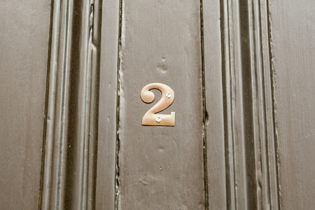 House number 2 sign on black painted door