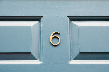 House number 6 sign on blue painted door Stock Photo