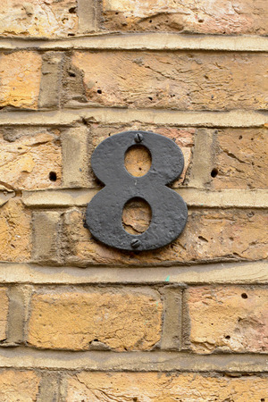 House number 8 sign fixed to wall Stock Photo