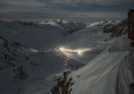deep powder snow: Night shot of the european alps with snow groomers