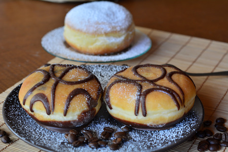 icing sugar: Traditional donuts with chocolate and icing sugar on the brown plate
