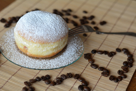 Fresh donut with powdered sugar on a plate on the table