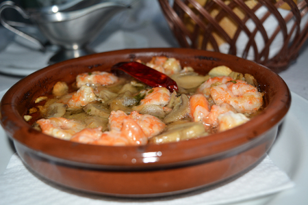 sizzling: Sizzling prawns with mushroom and garlic. Traditional Spanish tapas dish.