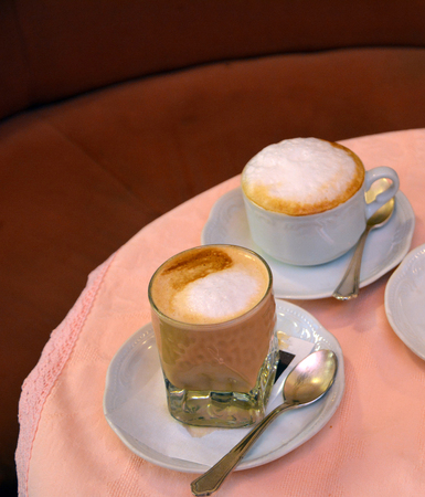 foamy: Delicious foamy cappuccino on a glass cup on a table