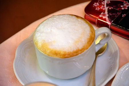 foamy: Delicious foamy cappuccino on a white cup on a table