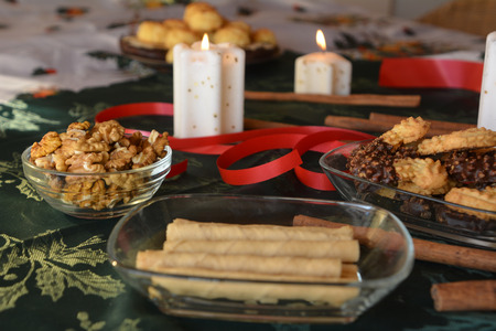 lighted: Christmas cookies with chocolate and nuts on a decorated table with lighted candles