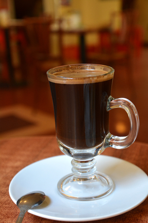 glass cup: Glass cup of a black coffee on a wooden table