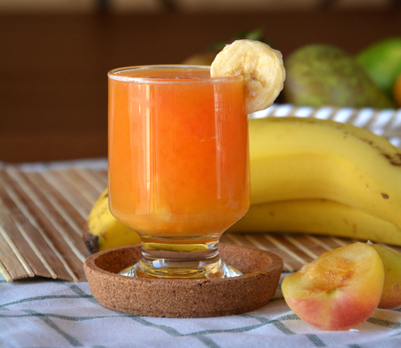 Fresh smoothie of orange, apricot and banana on a glass