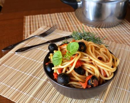 puttanesca: Spaghetti a la puttanesca on a bowl. Italian food.