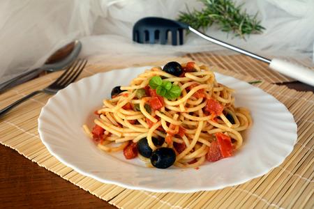 Delicious italian food spaghetti a la puttanesca on a bowl on a table. Stock Photo