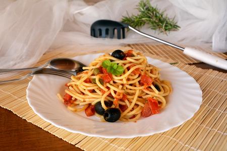 comida italiana deliciosa espaguetis a la puttanesca en un recipiente sobre una mesa. Foto de archivo