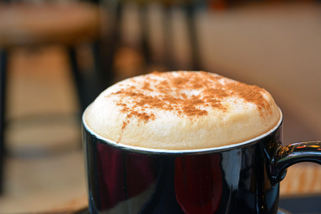 foamy: Delicious foamy cappuccino on a black cup on a plate
