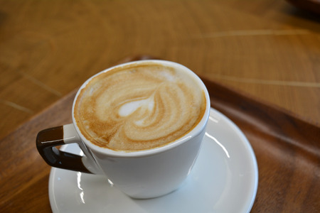 foamy: Delicious foamy cappuccino on a white cup on a plate