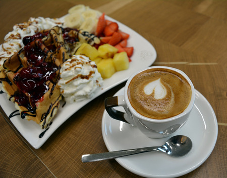 banana bread: Cup of foamy cappuccino and waffles with fruit and whipped cream