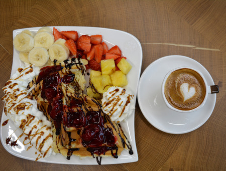 foamy: Cup of foamy cappuccino and waffles with fruit and whipped cream