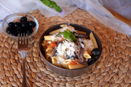 oily: Delicious italian food penne ala puttanesca on a bowl on a table. Stock Photo