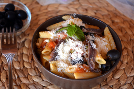 Delicious italian food penne ala puttanesca on a bowl on a table. Stock Photo