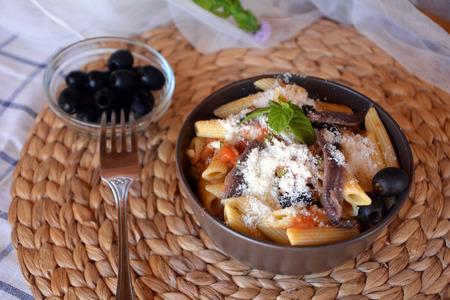 Deliciosa comida italiana penne ala puttanesca en un recipiente sobre una mesa.