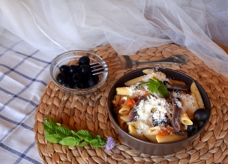 puttanesca: Delicious italian food penne ala puttanesca on a bowl on a table. Stock Photo