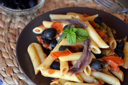 Delicious italian food penne ala puttanesca on a plate on a table.