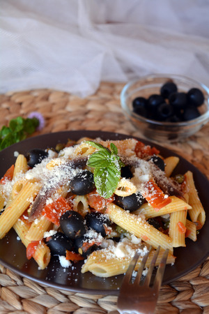 puttanesca: Delicious italian food penne ala puttanesca on a plate on a table.
