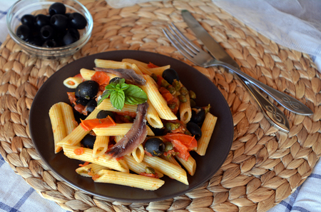 caper: Delicious italian food penne ala puttanesca on a plate on a table.