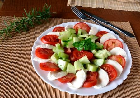 ensalada tomate: Fresh vegetable salad with mozzarella, tomato and basil on a plate