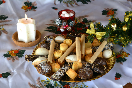 lighted: Christmas cookies with coconut on a table with lighted candles