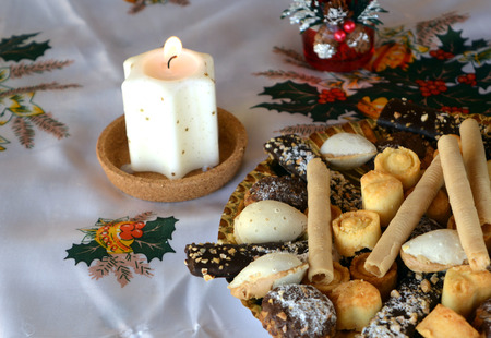Christmas cookies with coconut on a table with lighted candles
