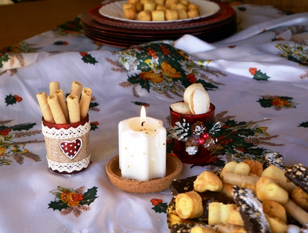 lighted: Christmas cookies on a plate and white lighted candle