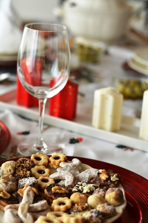 Christmas cookies with chocolate,nuts and coconut decorated on a plate on a table with wine glass