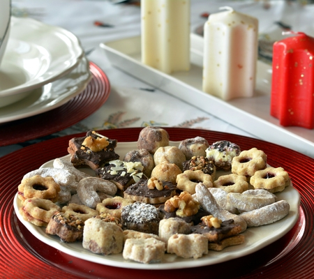 bisquit: Christmas cookies with chocolate,nuts and coconut decorated on a plate on a table with candles