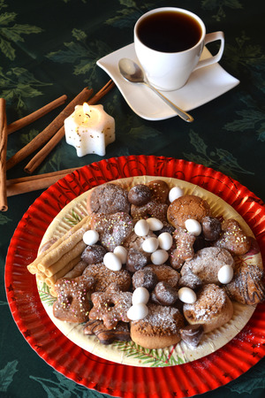 Detail of delicious Christmas cookies with cup of coffee on a table with candle on white tone.