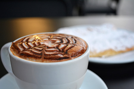 Delicious foamy cappuccino on a white cup on a plate. Stock Photo